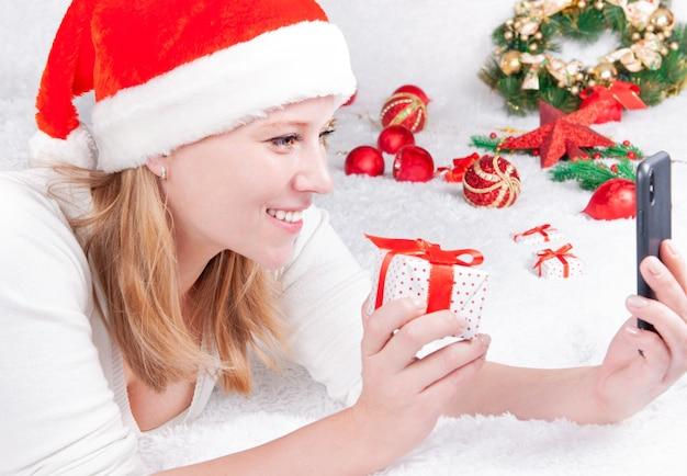 Weihnachten online glückwunsch. lächelnde frau mit smartphone für videoanruf freunde und eltern.