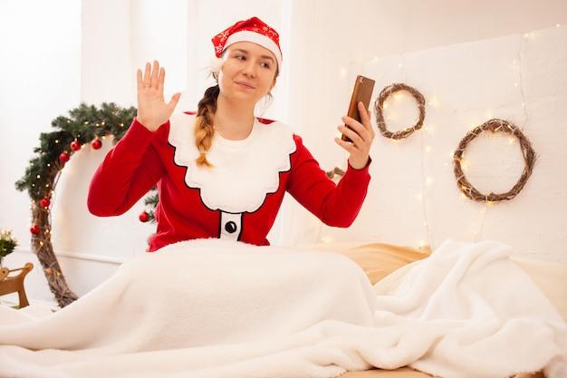 Weihnachten online herzlichen glückwunsch zum urlaub. die frau mit dem rad hält das telefon in der hand und kommuniziert per videoanruf mit ihren freunden und ihrer familie