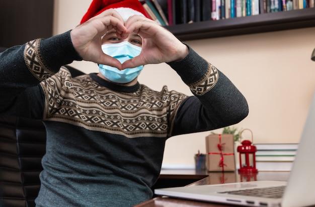 Weihnachten online liebe glückwunsch. junger mann im weihnachtsmannhut und in der gesichtsmaske spricht unter verwendung des laptops für videoanruffreunde und -kinder. weihnachten während des coronavirus.