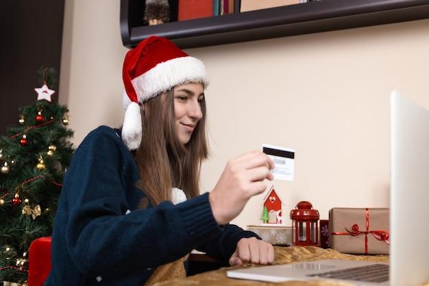 Weihnachten online-shopping. ein junges mädchen in einem weihnachtsmannhut und einem blauen pullover sitzt in der nähe eines laptops. das zimmer ist festlich eingerichtet.