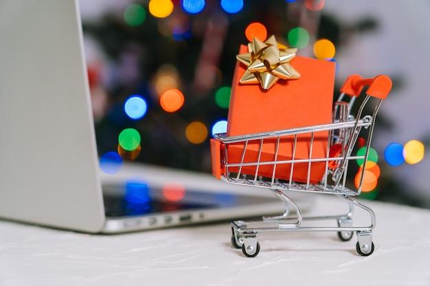 Weihnachten online-shopping. frau kaufen geschenke, bereiten sich auf weihnachten vor, zwischen einkaufswagen und geschenkbox. winterferien frohe weihnachten winterferien verkaufskonzept. selektiver fokus.