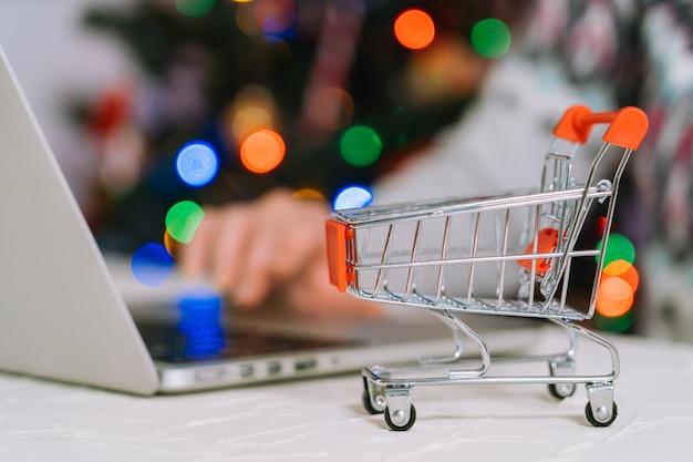 Weihnachten online-shopping. frau kaufen geschenke, bereiten sich auf weihnachten vor, zwischen einkaufswagen und geschenkbox