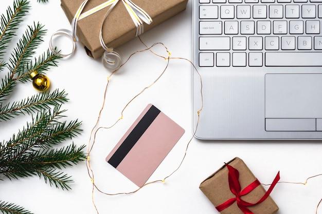 Weihnachten online-shopping-wohnung lag. ein offener laptop, eine kreditkarte, mit einem roten band gebundene geschenkboxen, grüne tannenzweige, sternengirlanden