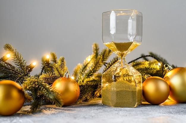 Weihnachten, sanduhr mit goldenem sand, tannenzweigen und weihnachtsspielwaren. das konzept des nahenden urlaubs. frohes neues jahr.