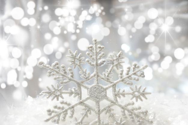 Weihnachten schneeflocke im schnee mit bokeh lichter eingebettet