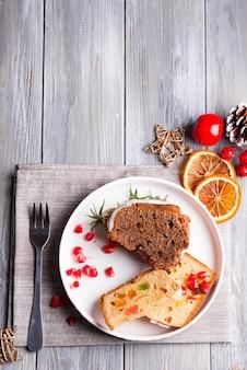 Weihnachten schnitt schokoladenkuchen und fruchtkuchen mit weißer zuckerglasur und granatapfelkernplatte mit dekoration auf einer hölzernen grauen, flachen lage