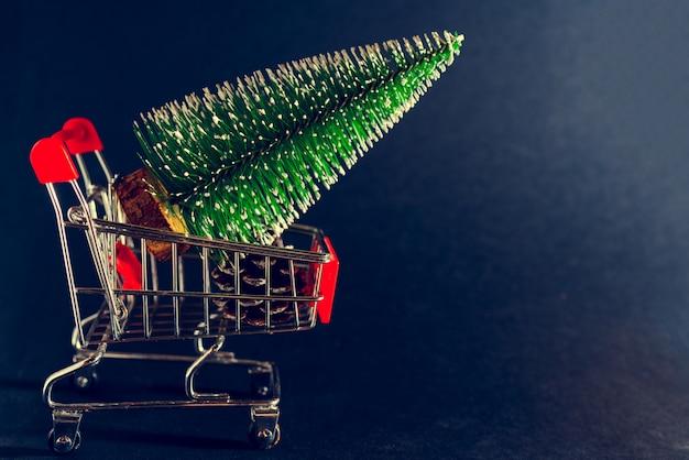 Weihnachten schwarz. supermarktwagen und weihnachtsbaum.