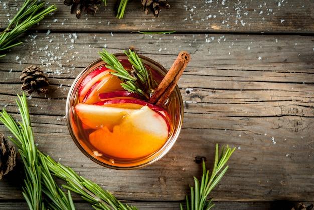 Weihnachten, thanksgiving-drinks. herbst, wintercocktailgrog, heiße sangria, glühwein - apfel, rosmarin, zimt, anis. auf altem rustikalem holztisch. mit zapfen, rosmarin. kopieren sie die draufsicht des raumes