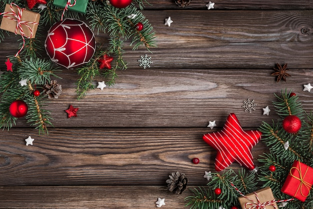 Weihnachten und ein frohes neues jahr hintergrund tannenbaumzweige mit roten verzierungen auf holztisch