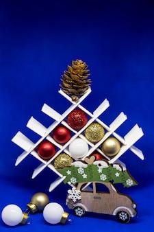 Weihnachten und ein glückliches neues jahr kreative dekorationen. feiertagsdekor. kreative komposition mit weihnachtsbaumspielzeug auf blauem hintergrund. feiertags- und feierkonzept für postkarte oder einladung.