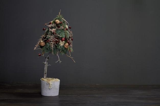 Weihnachten und komposition. weihnachtsbaum gemacht von den tannenzweigen und durch natürliche materialien und bälle in einem zementtopf verziert Premium Fotos