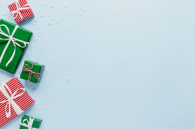 Weihnachten und neujahr blau flach mit verschiedenen roten, weißen und grünen geschenkboxen draufsicht. geschenkband und gestreiftes tabby-verpackungspapier. kopieren sie platz für text. foto in hoher qualität