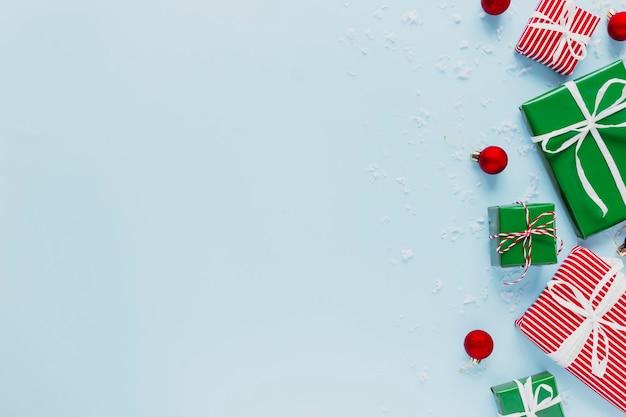 Weihnachten und neujahr blau flach mit verschiedenen roten, weißen und grünen geschenkboxen draufsicht. geschenkband und verpackungspapier. dekoration von schneeflocken, spielzeugbällen. leerzeichen-textbereich auf foto kopieren