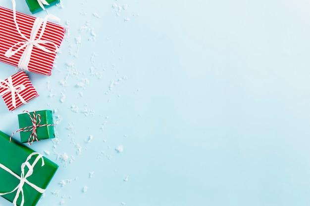 Weihnachten und neujahr blau flach mit verschiedenen roten, weißen und grünen geschenkboxen draufsicht. geschenkband und verpackungspapier. schneeflocken dekorieren. leerzeichen-textbereich kopieren. foto in hoher qualität