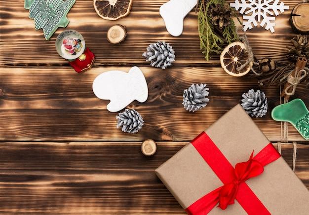 Weihnachten und neujahr. dunkler flacher holzrahmen mit geschenken, weihnachtsspielzeug und zapfen. speicherplatz kopieren.