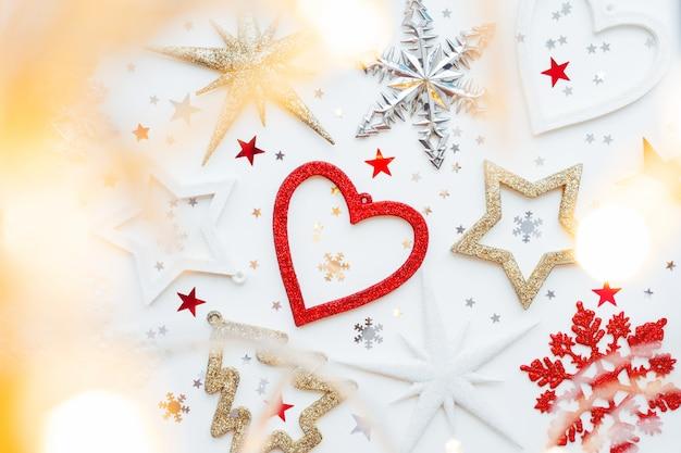 Weihnachten und neujahr mit funkelnder tanne, herz, schneeflocken und sternkonfetti.