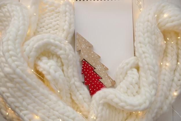 Weihnachten und neujahr. notizblock, roter holzbaum, weißer strickschal und leuchtende girlande