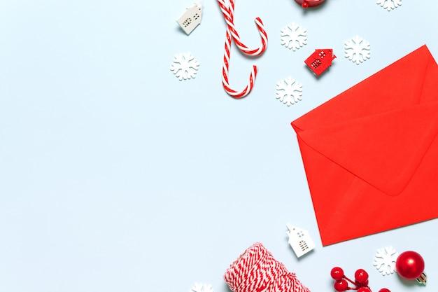 Weihnachten und neujahr rahmen aus roten beeren, baumwolle, schäbigen garnrollen, weihnachtskugeln, post, zuckerstange, haus und stern