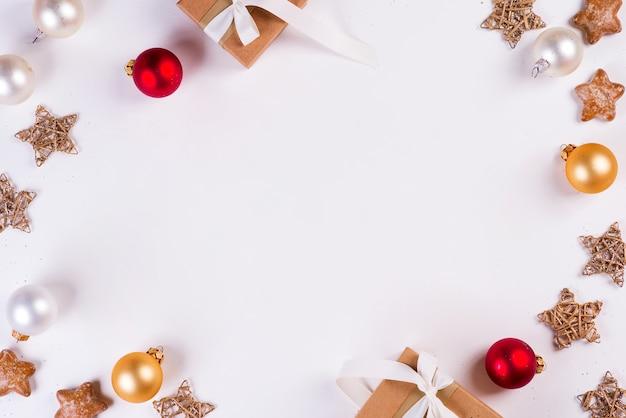 Weihnachten und neujahr urlaub zusammensetzung. modellrahmen mit geschenkbox, bällen und sternen. flachgelegt, draufsicht festlich.