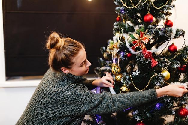 Weihnachten und neujahr vibes. hauptdekorationen. charmante junge frau in einer strickjacke