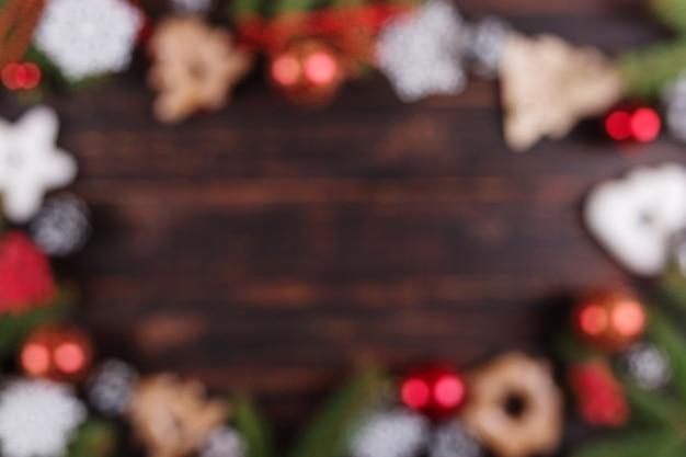 Weihnachten verwischte abstrakten hintergrund, weihnachtsbäume, dekorationen und handgemachte lebkuchenplätzchen auf einem holztisch