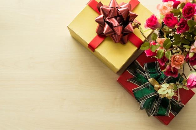 Weihnachten viele geschenke mit rosenvase und auf hölzernem innenraum der draufsicht. dekoration zu weihnachten und neujahr.