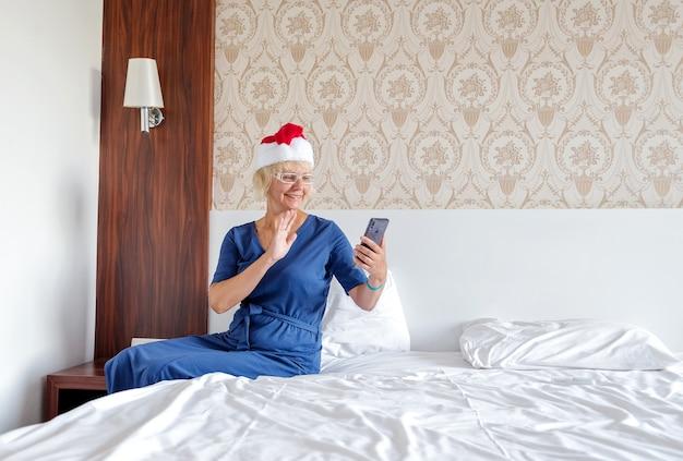Weihnachten, weihnachten, online-shop-konzept - eine frau in einem weihnachtsmann-helferhut mit einem smartphone.