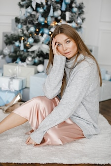 Weihnachten, weihnachten, winter, glückskonzept - lächelnde frau mit vielen geschenkboxen. mädchen öffnet ein geschenk vor dem hintergrund des weihnachtsbaumes. glückliche junge frau, die weihnachten feiert