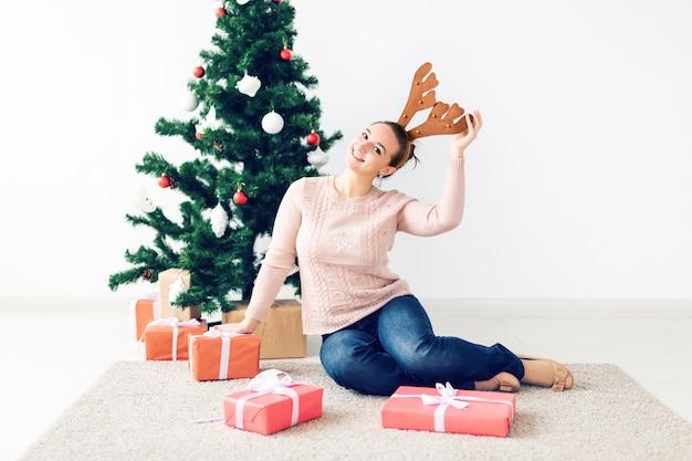 Weihnachten, weihnachten, winter, glückskonzept - mädchen öffnet ein geschenk vor dem hintergrund des weihnachtsbaums. glückliche junge frau, die weihnachten feiert