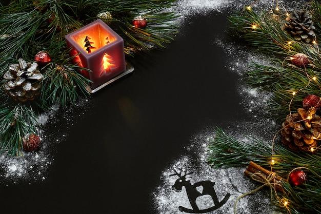 Weihnachten, weihnachtsbaum, kerze, schnee, kegel und zimtstangen auf schwarzem hintergrund. ansicht von oben. platz kopieren. stillleben. flaches neues jahr