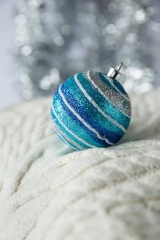 Weihnachten. weihnachtsspielzeug silber, blau gestreifte kugel mit glitzern auf einem weißen gestrickten wollpullover.