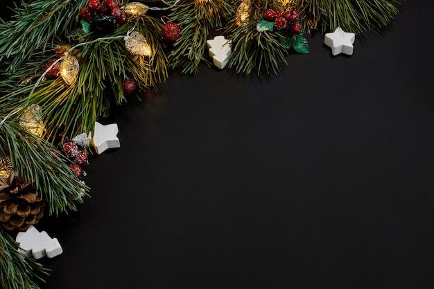 Weihnachten. weihnachtsspielzeug und fichtenzweig auf der draufsicht des schwarzen hintergrundes. platz kopieren. stillleben. flach liegen. neujahr