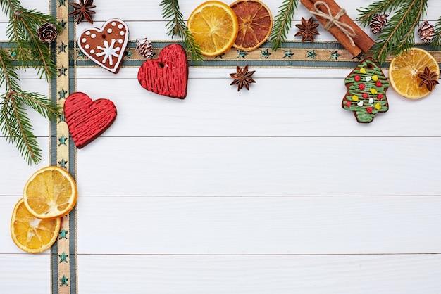 Weihnachten weißes holz mit hausgemachten weihnachtsplätzchen, band, weihnachtsbaum und zimt