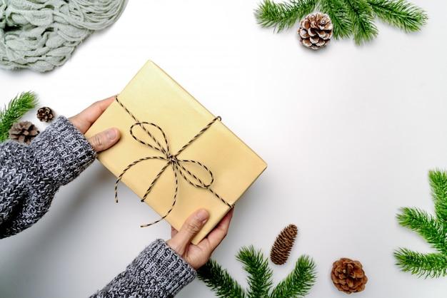 Weihnachten winter komposition. frauenhandgriff-weihnachtsgeschenkbox mit kiefernkegeln, tannenzweige auf weißem hintergrund. flache lage, draufsicht, kopienraum