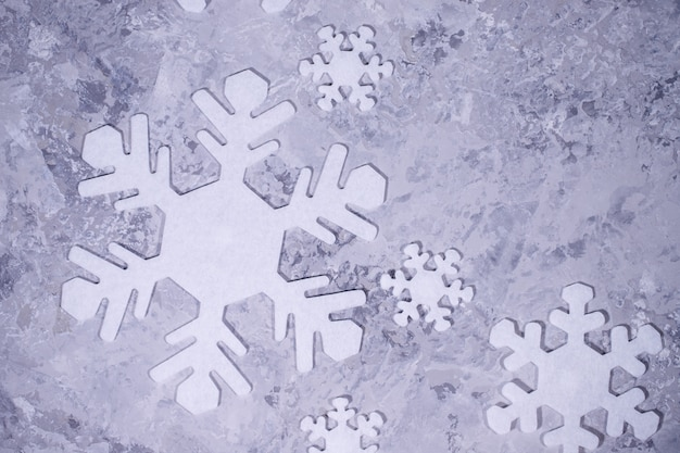 Weihnachten, winter, neujahrskonzept. grauer hintergrund mit weißen schneeflocken. flachgelegt, draufsicht