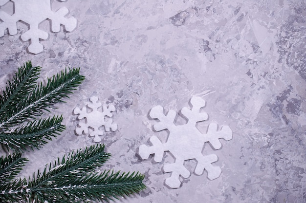 Weihnachten, winter, neujahrskonzept. grauer hintergrund mit weißen schneeflocken und tannenzweigen. flachgelegt, draufsicht