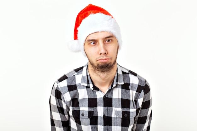 Weihnachten, winterferien und leutekonzept - lustiger mann im weihnachtsmann-hut über weißem hintergrund.
