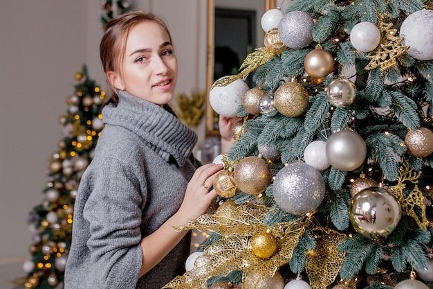Weihnachten, winterferien und menschenkonzept - glückliche junge frau, die weihnachtsbaum zu hause verziert.