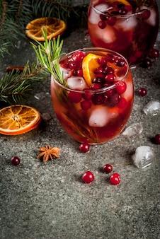 Weihnachten wintergetränke. kaltes cocktail mit moosbeeren, orange, rosmarin, mit gewürzen (zimt, anis) und eis, auf einer dunklen steintabelle, copyspace