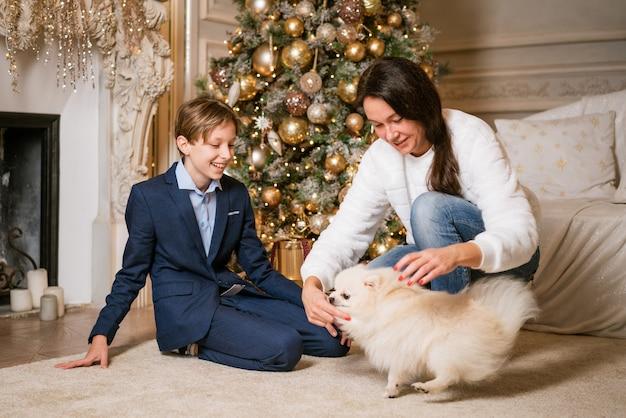 Weihnachten zu hause sohn und mutter und hund unter baum ein junge und eine frau spielen mit einem tierfeier ...