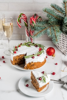 Weihnachtlicher obstkuchen oder pudding, dekoriert mit rosmarin und preiselbeeren, mit weihnachtsdekoration, auf weissem marmortisch,