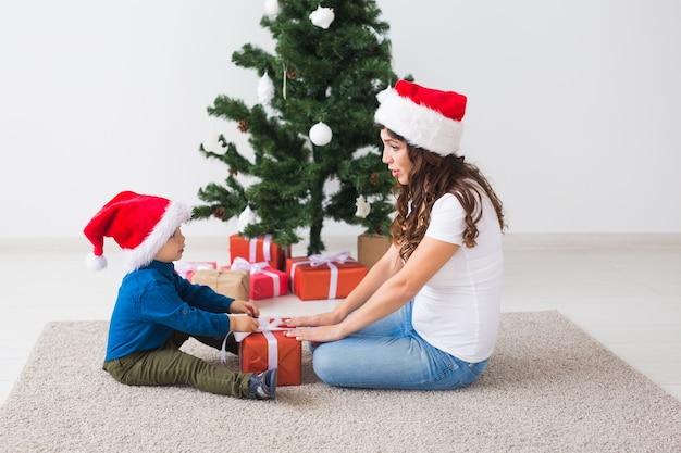 Weihnachts-, alleinerziehendes und feiertagskonzept - netter kleiner junge, der weihnachtsgeschenk für sein hält
