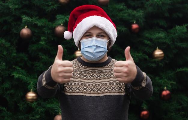 Weihnachts daumen hoch wie zeichen. schließen sie herauf porträt des mannes, der einen weihnachtsmannhut, weihnachtspullover und medizinische maske mit emotion trägt. vor dem hintergrund eines weihnachtsbaumes. coronavirus pandemie