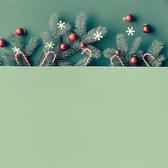Weihnachts-draufsicht mit tannenzweigen verziert mit roten kugeln, zuckerstangen, papiersternen, textraum