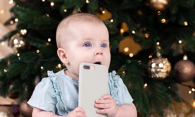 Weihnachts entzückendes kleines baby, das am telefon spricht. babykindporträt auf dem hintergrund des weihnachtsbaumes. weihnachten süßes kleinkind.
