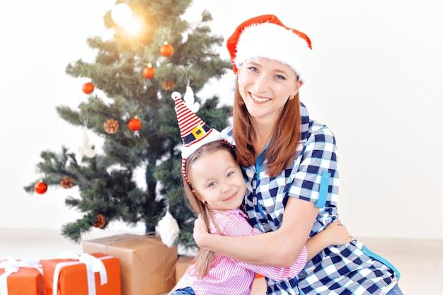 Weihnachts-, familien- und urlaubskonzept - festliche mutter und tochter auf der couch zu hause im wohnzimmer