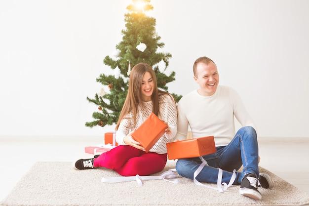 Weihnachts-, feiertags- und feierkonzept - hübscher junger mann und hübsche junge frau, die auf dem teppich sitzen und eine geschenkbox halten.