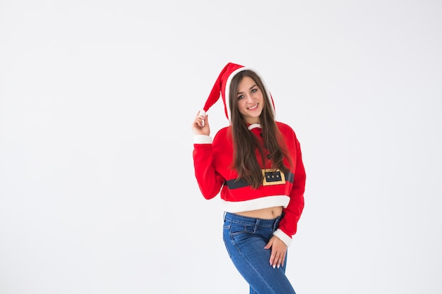Weihnachts-, feiertags- und personenkonzept - glückliche reizende junge frau im weihnachtsmannkostüm auf dem weißen raum mit kopienraum