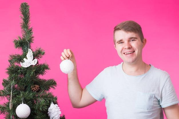 Weihnachts-, feiertags- und personenkonzept - junger glücklicher mann zeigen weihnachtsdekorationen auf weihnachtsbaum über der rosa wand