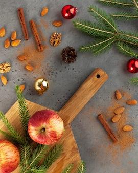 Weihnachts-flatlay aus äpfeln, nüssen, zimt und ästen. das konzept von weihnachten und neujahr. grußkarte.